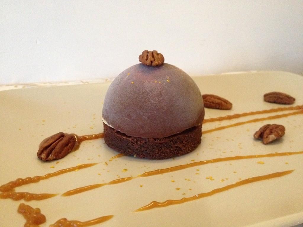 dôme chocolat au lait, garni d'une glace maison vanille pécan caramel au beurre salé, sur un socle de brownies aux noix de pécan